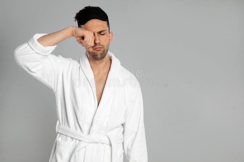 Sleepy young man in bathrobe on grey background. Space for text stock image