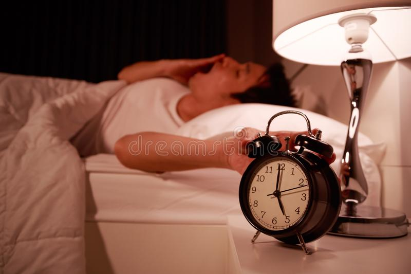 Sleepy young man in bed with extending hand to alarm clock in morning royalty free stock image