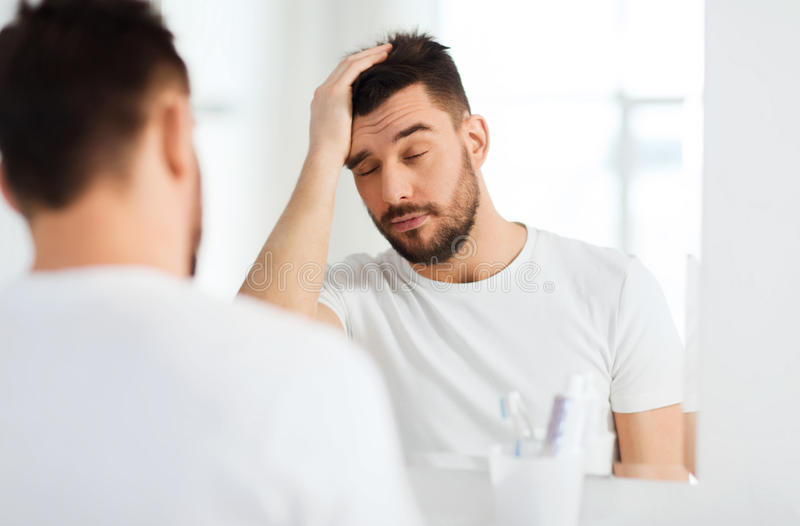 Sleepy young man in front of mirror at bathroom royalty free stock photography