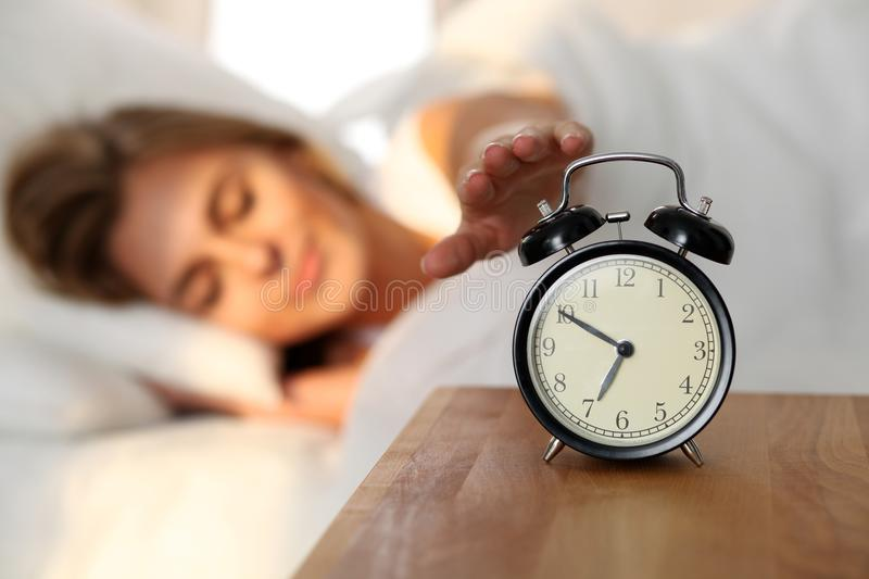 Sleepy young woman stretching hand to ringing alarm willing turn it off. Early wake up, not getting enough sleep royalty free stock image