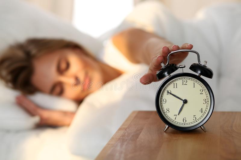 Sleepy young woman stretching hand to ringing alarm willing turn it off. Early wake up, not getting enough sleep stock photos