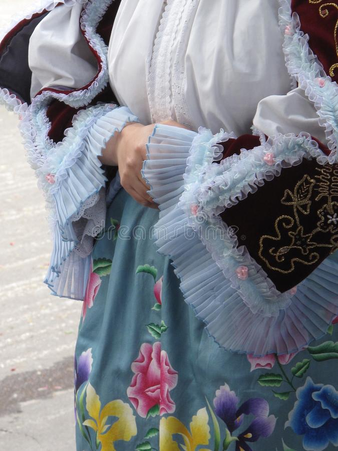 Sleeves with laces and a colored gown with flowers. Detail of traditional Sardinian garments during the St. Efisio parade in Cagliari on May 1st stock photos
