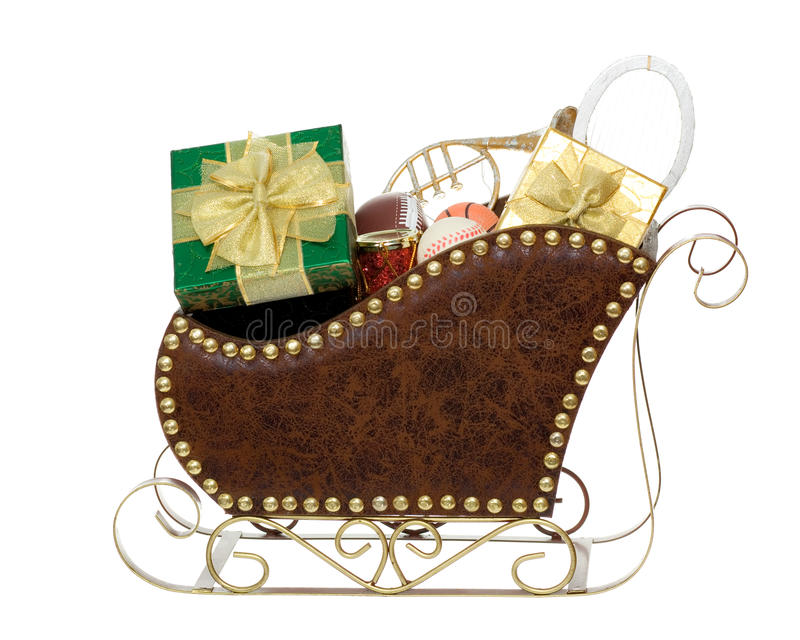 Sleigh Full of Presents and Toys. Brown Christmas Sleigh filled with green present, gold present, baseball, football, basketball, tennis racket, trumpet, and red royalty free stock photography