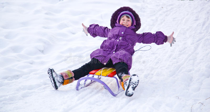 A sleigh. Happy girl riding a sleigh stock image