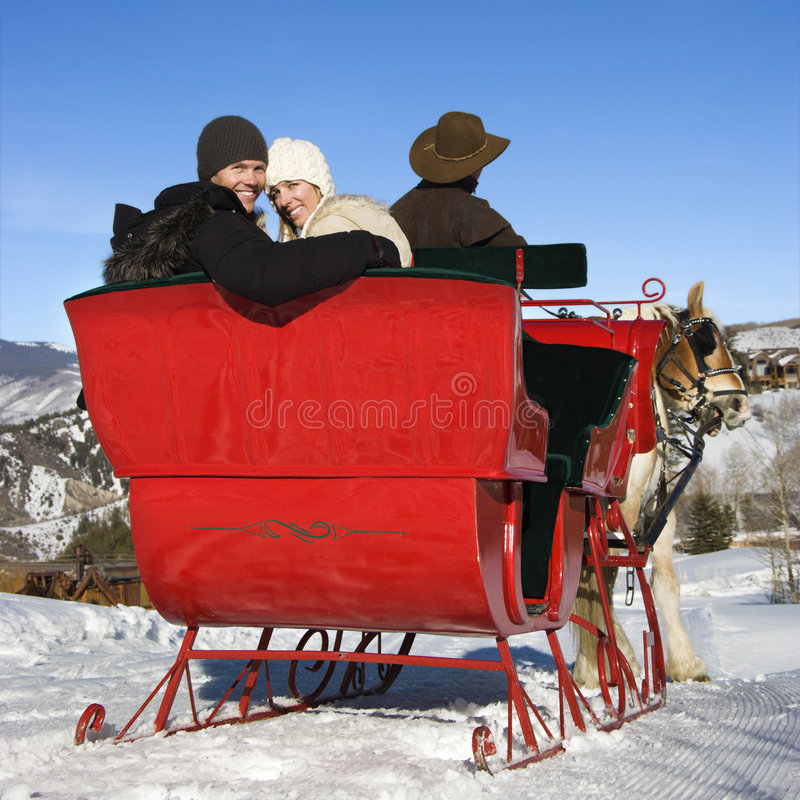 Sleigh ride. Mid-adult Caucasian couple taking a sleigh ride lookingback to viewer royalty free stock image