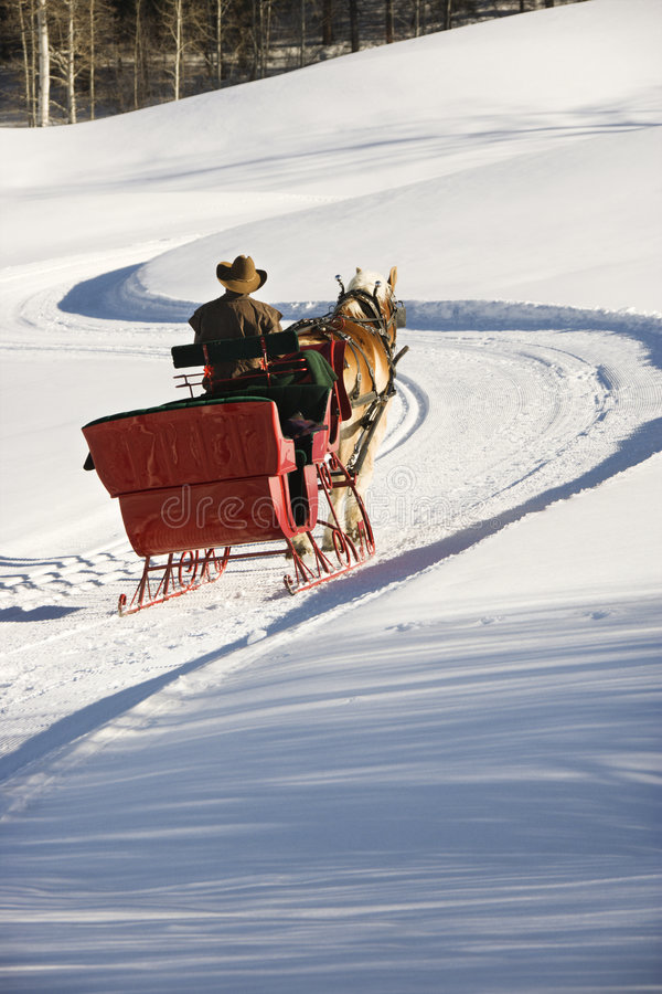Sleigh ride. Man driving sleigh up a snow covered hill royalty free stock images