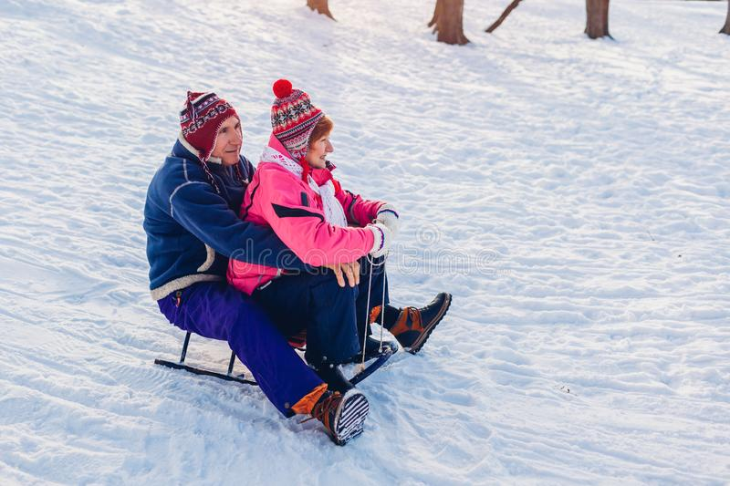 Sleigh. Senior couple sledding down. Family having fun in winter park. Valentine`s day. Winter activities royalty free stock images