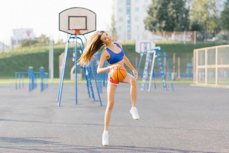 Slender athletic girl in short shots and top plays with a basketball royalty free stock photo