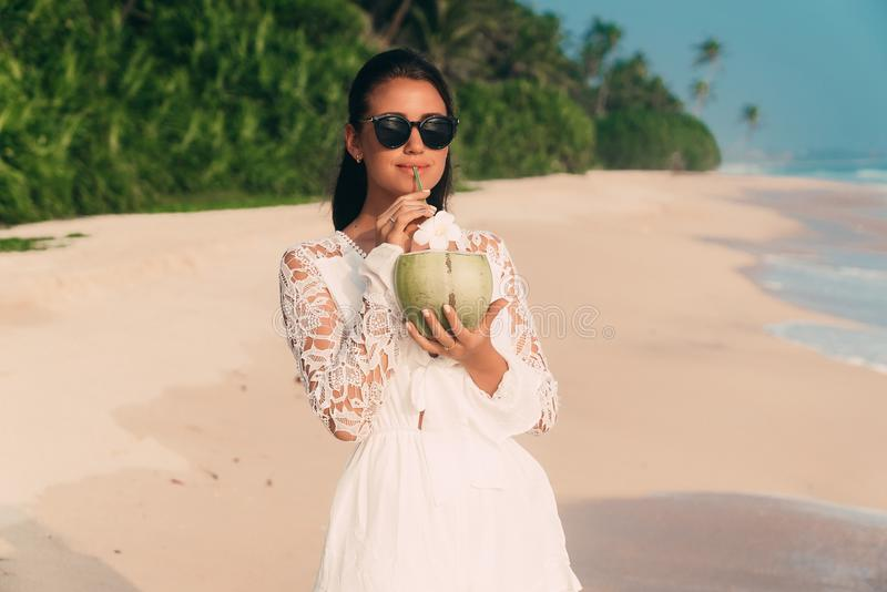 Slender attractive dark-haired girl strolls along the seashore, wears a stylish tunic and sunglasses, drinks a delicious royalty free stock image