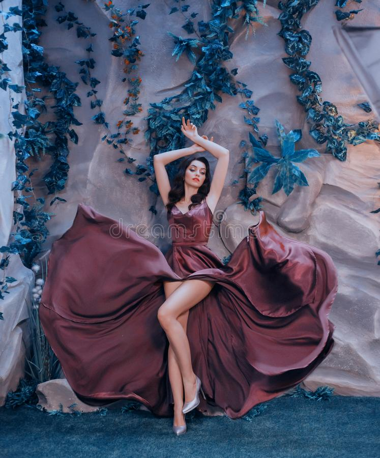 Slender attractive lady like picture of gorgeous artist, flying fluttering marsala long satin dress like paint strokes. Girl elegantly raised her arms top royalty free stock images