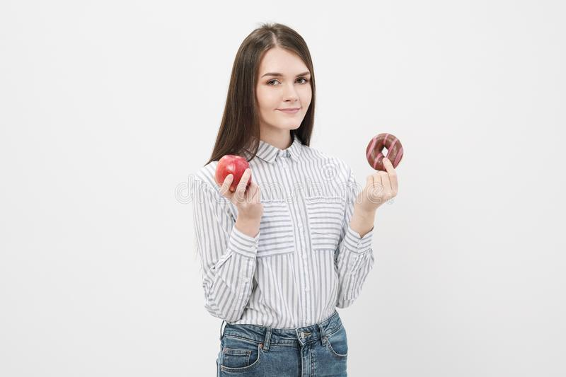 A slender beautiful brunette girl on a white background holding a pink glazed donut and a red apple. royalty free stock image
