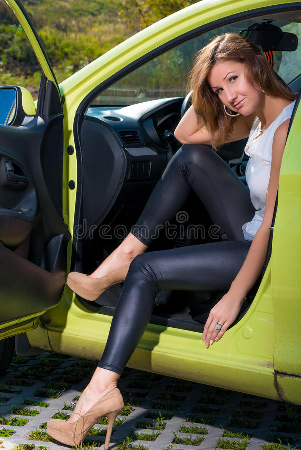 Slender beautiful car driver behind the wheel royalty free stock images