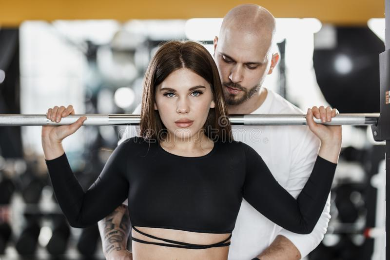 Slender beautiful girl is doing back squats and strong athletic man insures her in the modern gym royalty free stock images