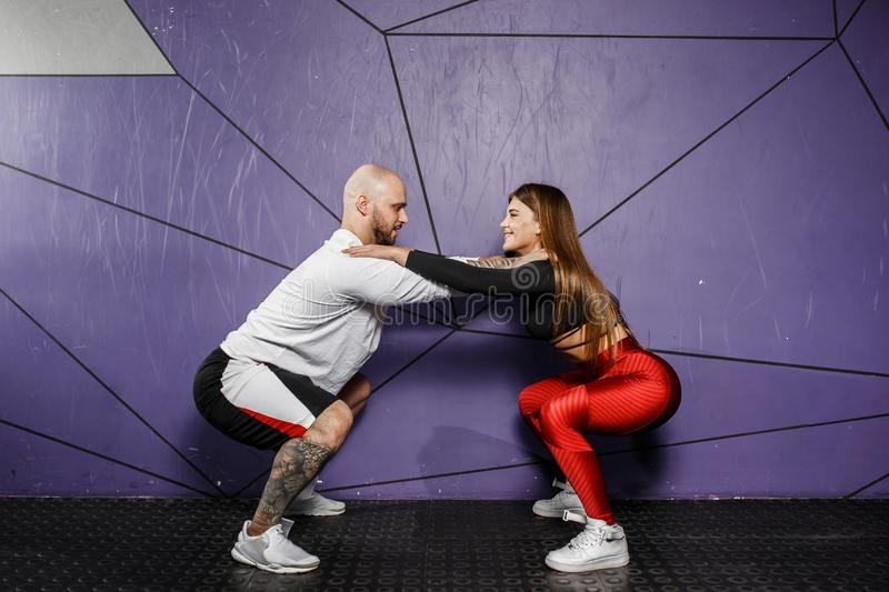 Slender beautiful girl in stylish sports clothes and strong athletic man do squats on the background of stylish violet stock photo