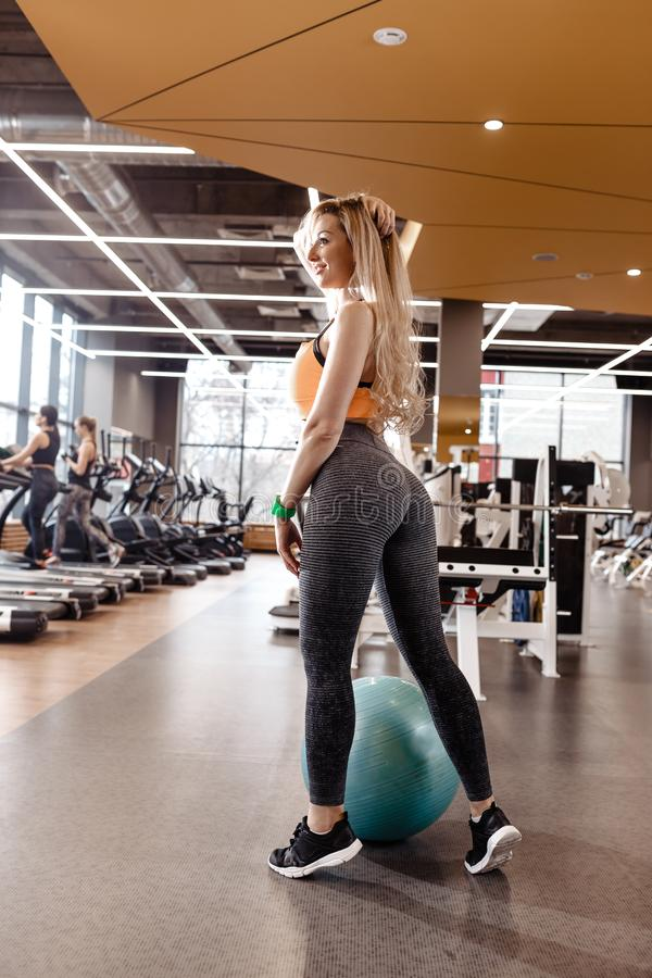 Slender blond girl with long hair dressed in a sportswear is posing next to the fitness ball in the modern gym with a royalty free stock images