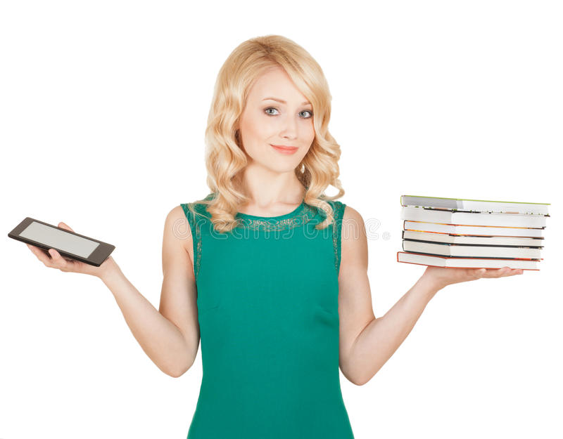 Slender blonde compares a tablet and books royalty free stock photos