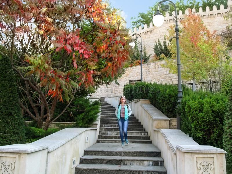 Slender blonde girl descends the stairs against of a copy of the wall of Baku fortress and oriental plants in Heydar Aliyev Park stock photo