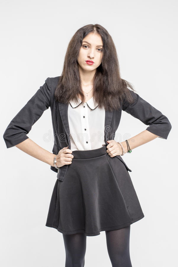 Slender brunette girl removes a business suit undressing royalty free stock image