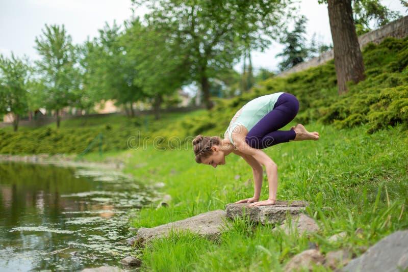 Slender Caucasian brunette girl doing yoga in summer on a green lawn by the river. woman doing Crane exercise, Bakasana pose stock photography