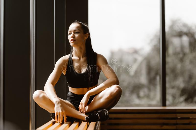 Slender dark-haired girl dressed in black sports top and shorts is sitting in lotus pose on a wooden window sill in the stock photo