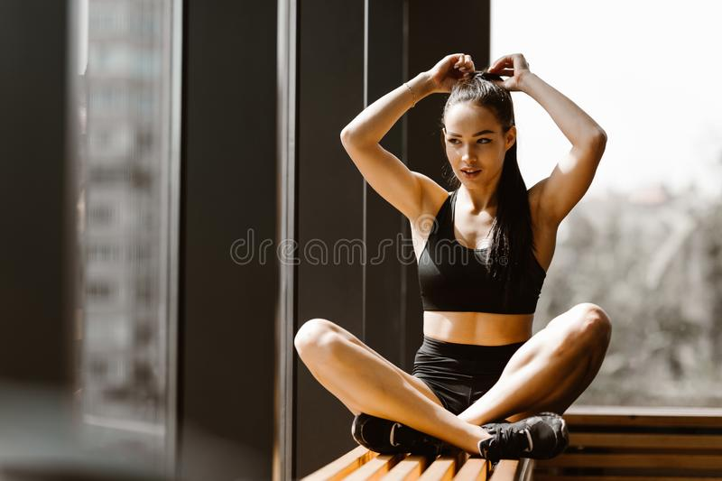 Slender dark-haired girl dressed in black sports top and shorts is sitting in lotus pose on a wooden window sill in the royalty free stock photos
