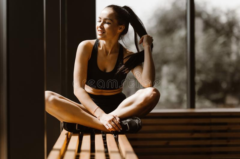 Slender dark-haired girl dressed in black sports top and shorts is sitting in lotus pose on a wooden window sill in the royalty free stock image