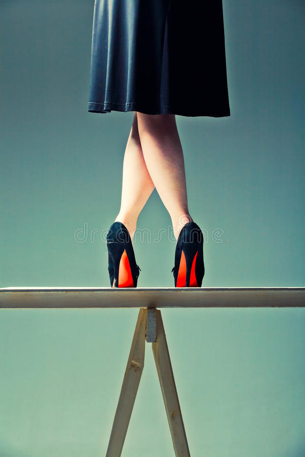 Slender female legs crossed on the table. Slender female legs crossed in the shoes with red soles on the table stock photo