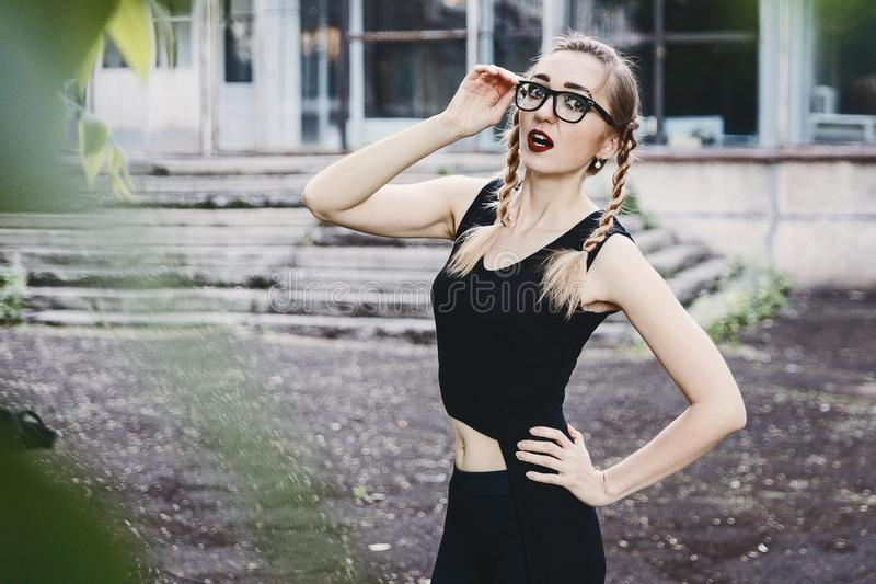 Slender girl in black dress with pigtails and glasses stock photography