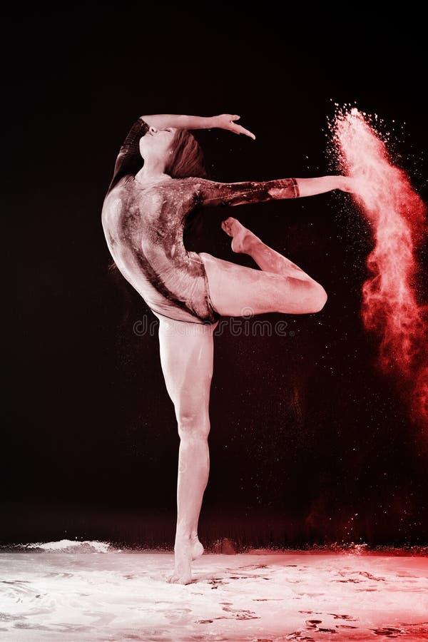 Slender blonde dancing in white dust studio shot royalty free stock images