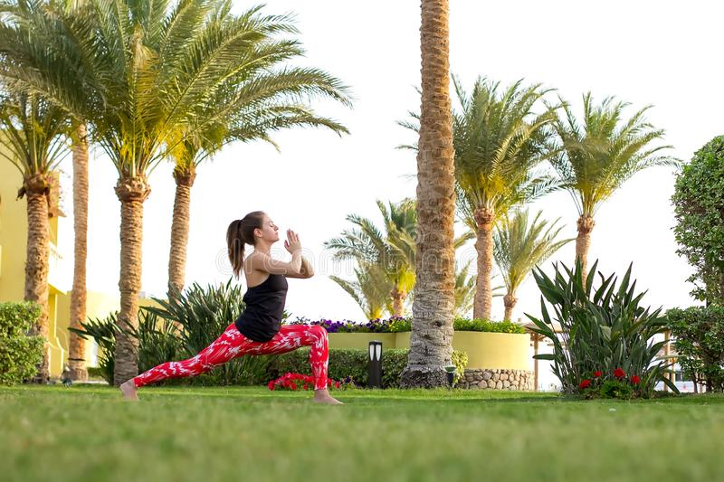 Slender girl does yoga exercises in the early morning at the resort. Healthy lifestyle. stock photo