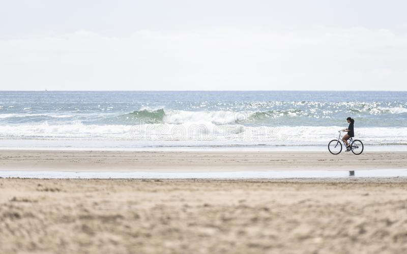 Slender girl rides a bicycle breathing fresh sea air riding along the Pacific Ocean royalty free stock photo