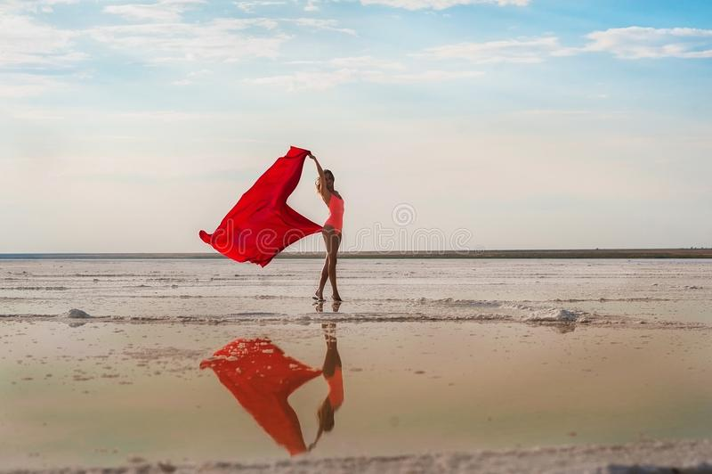 Slender girl on the salt lake of Elton, Volgograd region, Russia. Lake Elton. A girl in a red bathing suit and pareo, the fabric d stock photography