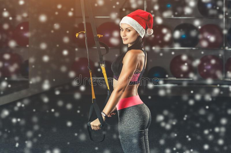 A slender girl in santa claus hat holds a strap in her hand for the suspension training on snowflakes background in the gym. TRX exercises. Sports concept and royalty free stock images