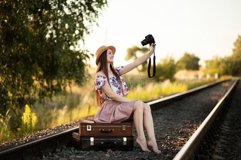 A slender girl in a straw hat is sitting on a suitcases on the railroad tracks, holding a camera and taking pictures of herself. stock image