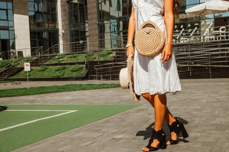 Slender girl in a white chintz dress holds a woven straw round bag in her hands royalty free stock images