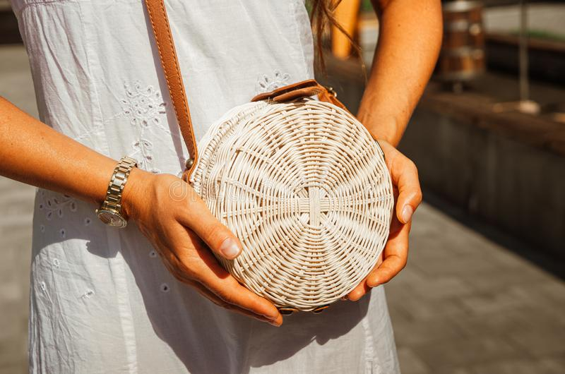 Slender girl in a white chintz dress holds a woven straw round bag in her hands stock images