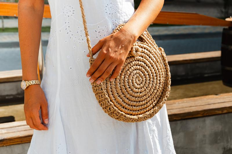 Slender girl in a white chintz dress holds a woven straw round bag in her hands royalty free stock photos
