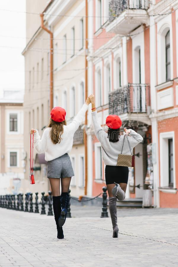 Slender girlfriends in a short skirt and shorts, red berets and with bags in their hands, holding hands that raised up. They enjoy stock images