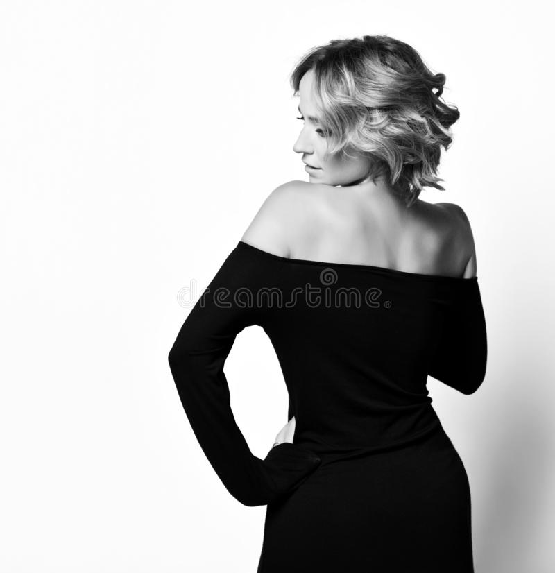Slender lady with curly blonde hair in stylish black dress standing with her back to us, turning her head to the side stock photography