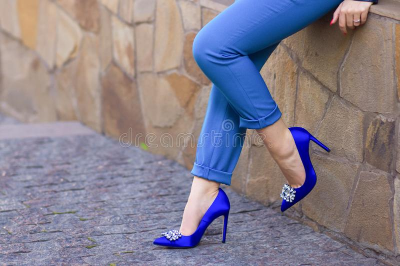 Slender legs in blue breeches and heels. On a hairpin stock images