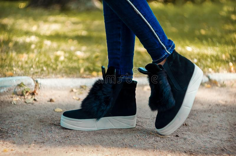 Slender legs in jeans shod in trend boots with fur and ears on a white thick sole. Slender legs in jeans shod in trendy black suede boots with fur and ears on a stock photography