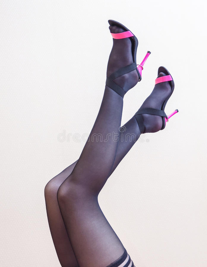 Slender legs of woman in stockings and heels stock photos