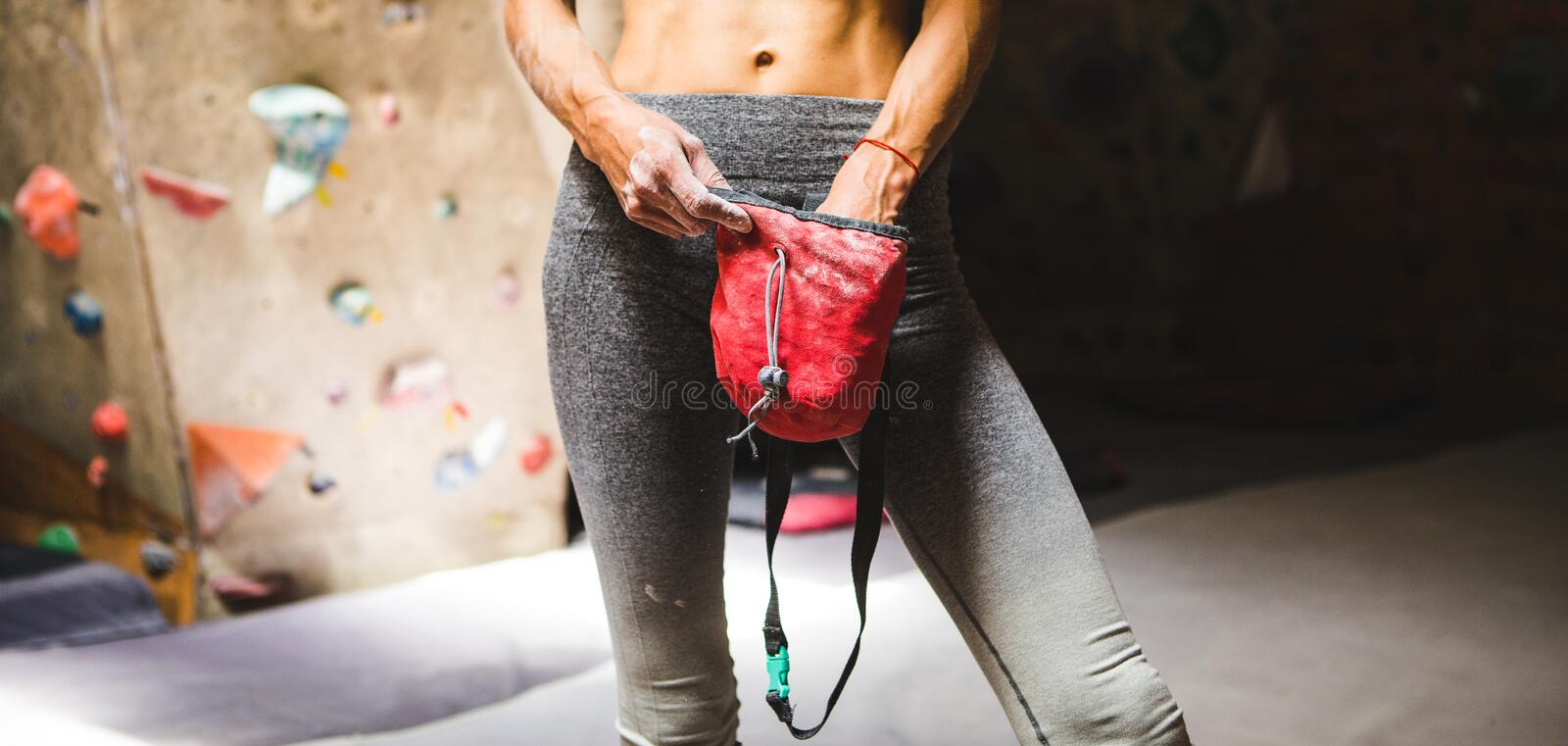 Slender rock climber holds a bag of magnesia stock photo