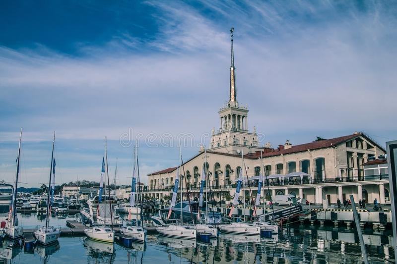 A slender row of yachts in the port of Sochi. Black Sea. The ships are moored. The reflection in the water. The main building of the seaport in Sochi. Sochi royalty free stock photo