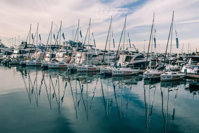 A slender row of yachts in the port of Sochi. Black Sea. The ships are moored. The reflection in the water. The main building of the seaport in Sochi. Sochi stock photography