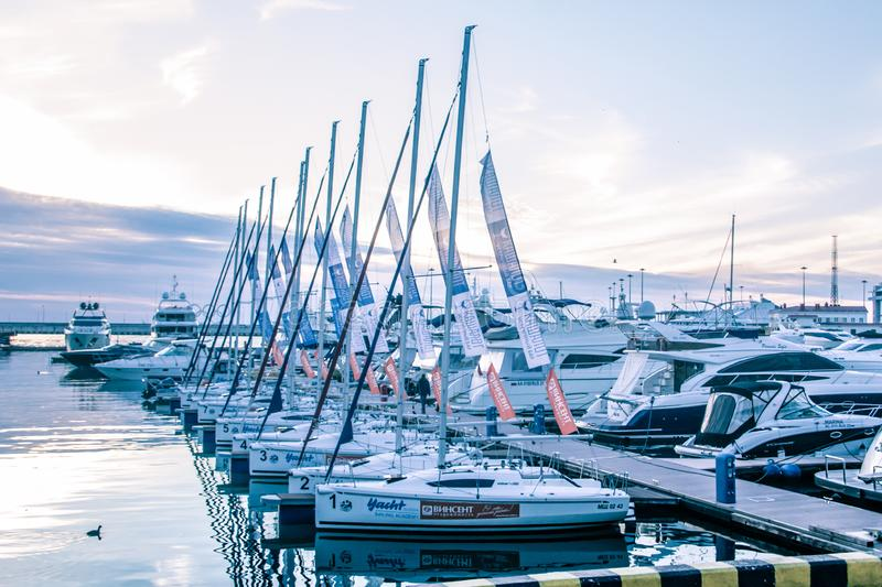 A slender row of yachts in the port of Sochi. Black Sea. The ships are moored. The reflection in the water. The main building of the seaport in Sochi. Sochi royalty free stock photos