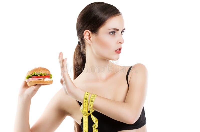 Slender sweet girl refuses to eat a hamburger. Isolation on a white background royalty free stock photo
