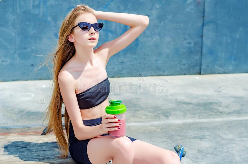 Slender teenager girl in sports top and shorts on playground for skaters in sunglasses and fitness cup in hand royalty free stock images