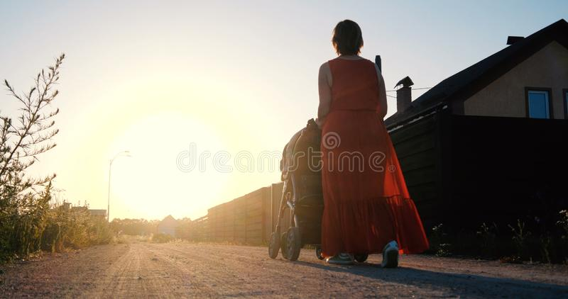 Slender woman in a red dress riding a baby in a pram at sunset stock photos