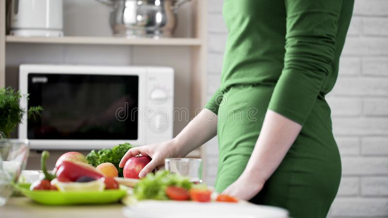 Slender woman taking fresh red apple from table, healthy nutrition, breakfast royalty free stock image